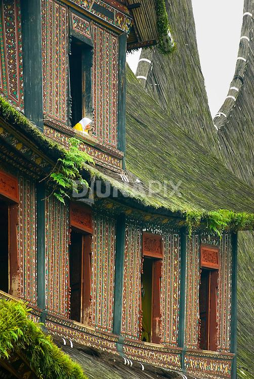 Woman peers from window opening at the towering Pagaruyung Palace, Batusangkar, West Sumatra.
