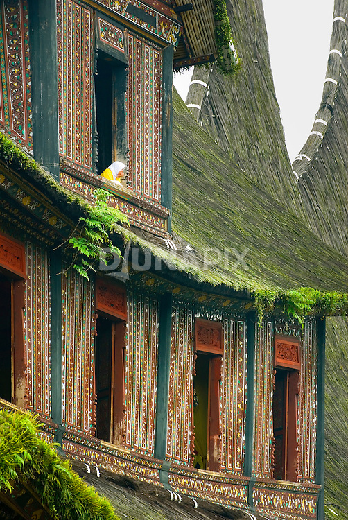 Woman peers from window opening at the towering Pagaruyung Palace, Batusangkar, West Sumatra.
