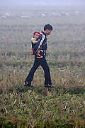 Hilltribe villages around Sapa. Red Dzao father and child in a paddy field.