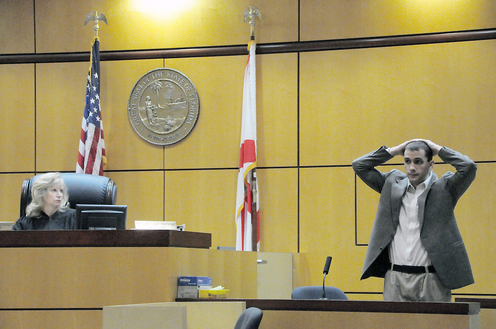 Andrew Knapp, FLORIDA TODAY -- Oct. 13, 2011 -- During his testimony Thursday morning in Circuit Judge Morgan Laur Reinman's Viera courtroom, Christopher Eddy shows how he held his hands over his head per the instructions of state wildlife Officer Vann Streety before he opened fire on Streety during a 2009 traffic stop.