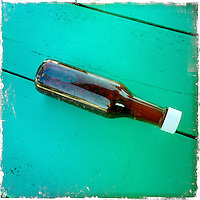 2013 May 13:  Hotsauce bottle on green wood. iPhone, Hipsta