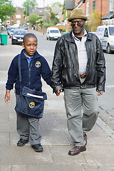 Little boy being collected from primary school by his grandfather,