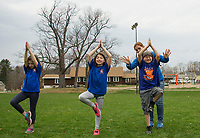 Elm Street School students participate in the school wide Tiger Trek on Friday morning at Leavitt Park.  Catrina Gray leads the school with a cool down yoga as Miss Perelli assists Brady in holding a tree pose.   (Karen Bobotas/for the Laconia Daily Sun)