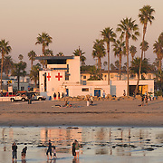 People stand in the wet sand in front of the life guard station, watching the sunset.  Ocean Beach, San Diego, California.