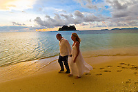 Couple walking on the beach after their sunset wedding ceremony, Vomo Island Resort, Fiji Island