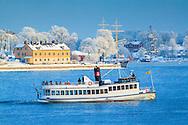 Båt med turister på Stockholms Ström  en vacker vinterdag med snö och frost i träden på Skeppsholmen i Stockholm.