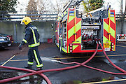 London Fire Brigade, station training session. A Fire fighter connects the hoses to the fire engine.