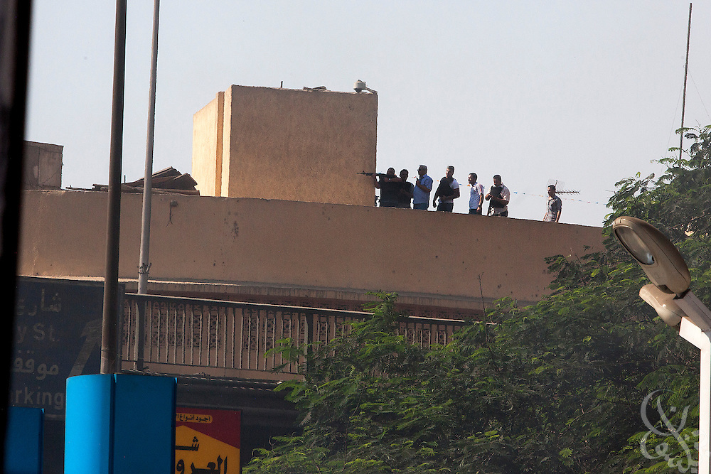 """What appear to be plainclothes security personnel (wearing bullet-proof vests usually issued to police) fire a rifle at nearby supporters of deposed Egyptian President Mohamed Morsi during intense street clashes August 16, 2014 for the """"Day of Rage"""" protests in Cairo, Egypt."""