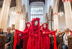 """© Licensed to London News Pictures. 19/07/2019; Bristol, UK. Extinction Rebellion Summer Uprising 2019. The """"Red Brigade"""" perform in St Stephen's Chuch at the closing ceremony for Extinction Rebellion in Bristol at the end of their 5 day protest in the city centre. Extinction Rebellion are holding a five-day 'occupation' of Bristol, by occupying Bristol Bridge in the city centre and traffic has to be diverted and carrying out other events. As part of a country-wide rebellion called Summer Uprising, followers will be holding protests in five cities across the UK including Bristol on the theme of water and rising sea levels, which is the group's focus for the South West. The campaign wants the Government to change its recently-set target for zero carbon emissions from 2050 to 2025. Photo credit: Simon Chapman/LNP."""