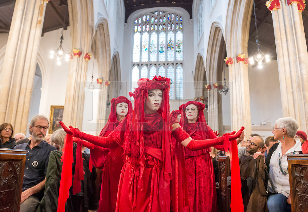 "© Licensed to London News Pictures. 19/07/2019; Bristol, UK. Extinction Rebellion Summer Uprising 2019. The ""Red Brigade"" perform in St Stephen's Chuch at the closing ceremony for Extinction Rebellion in Bristol at the end of their 5 day protest in the city centre. Extinction Rebellion are holding a five-day 'occupation' of Bristol, by occupying Bristol Bridge in the city centre and traffic has to be diverted and carrying out other events. As part of a country-wide rebellion called Summer Uprising, followers will be holding protests in five cities across the UK including Bristol on the theme of water and rising sea levels, which is the group's focus for the South West. The campaign wants the Government to change its recently-set target for zero carbon emissions from 2050 to 2025. Photo credit: Simon Chapman/LNP."