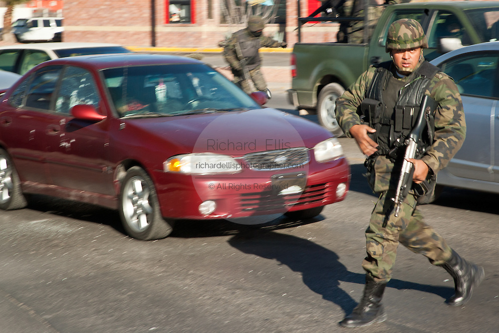 Mexican Army Soldiers respond to a assignation along a main road in Juarez, Mexico January 16, 2009 moments after armed gunman shot dead a former police officer during morning rush hour as the dead man lies behind the wheel in the red car. The shooting, believed linked to the ongoing drug war which has already claimed more than 40 people since the start of the year. More than 1600 people were killed in Juarez in 2008, making Juarez the most violent city in Mexico.    (Photo by Richard Ellis)