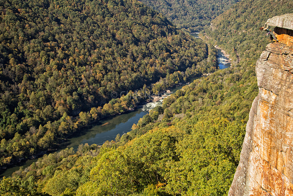 "Elaina Arenz climbing above the New River on ""Photo Finish"" 5.9, at Beauty Mountain in the New River Gorge"