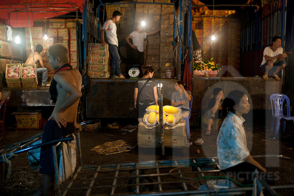 Workers organizing goods in the Long Bien Night Market, Hanoi, Vietnam