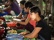 """25 OCTOBER 2015 - INSEIN, MYANMAR:  Women cut ginger into strips before selling it at Danyin Market (also known as Da Nyin) in Insein, Myanmar, about 90 minutes from Yangon. Ginger is frequently used for seasoning in Myanmar foods. Vendors in the market sell just about everything people in the area need, but mostly it's a """"wet market"""" with fruits, vegetables and meats. Most people in Myanmar still do not have refrigerators in their homes, so people go to market almost every day.    PHOTO BY JACK KURTZ"""