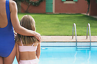 Mother and daughter (5-6) in swimwear by pool back view