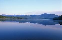Mt. Chocorua at dawn as seen from Chocorua Lake.  Mallard ducks swim in the foreground.  White Mountains. Tamworth, NH