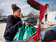"""17 MARCH 2020 - DES MOINES, IOWA:  JAELA DAVISON, 13, puts bags of food she got at a food distribution in the parking lot of Carver Elementary School in Des Moines. Des Moines Public Schools are closed for at least 30 days because of the Coronavirus outbreak. Des Moines area religious organizations and food banks are working together to bring free food to children in at risk communities. Volunteers and workers are practicing """"social distancing"""" by leaving the food packages on the pavement and recipients pick up the packages. Tuesday, the Governor of Iowa ordered all restaurants and bars to close or go to take out only. The Iowa Department of Public Health has urged all public buildings, like libraries and schools, to close, and all schools in Iowa are closed for at least 30 days.   PHOTO BY JACK KURTZ"""