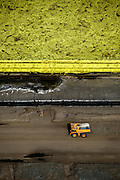 A dump truck races by a mountain of sulfur at one of the oil sand mines in Fort McMurray in Alberta, Canada. The sulfur is a byproduct from the refining of the  bitumen and represents a huge problem of its own. As of 2006 there were 15 million tons of sulfur stockpiled at the mining sites, and the price tag for maintaining the toxic runoff is hefty. The Athabasca oil sands deposit is among the largest in the world.  The bitumen, also commonly named tar (hence tar sands), contains lots of hydrocarbons, but is notoriously hard to extract. For every 100 BTU of energy extracted, 70 BTU is lost in the process. In 2011 alone, the oil sands operations in Canada produced 55 million tons of 'greenhouse gas emissions'. That's eight percent of Canada's total emissions.