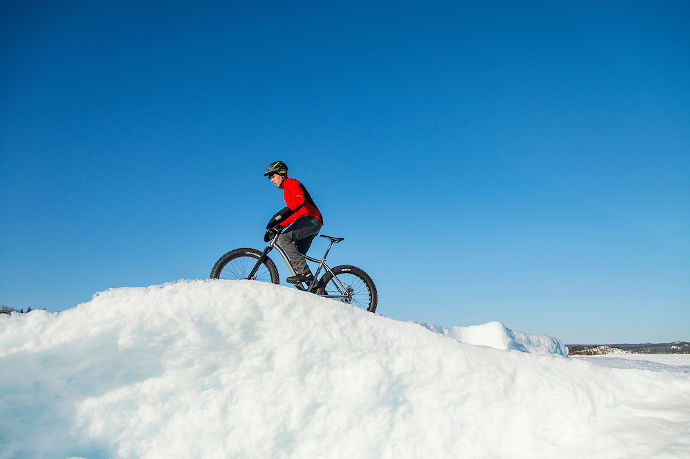 Ryan Labar rides the frozen shoreline of Lake Superior on a fat bike snow bike at Marquette, Michigan.