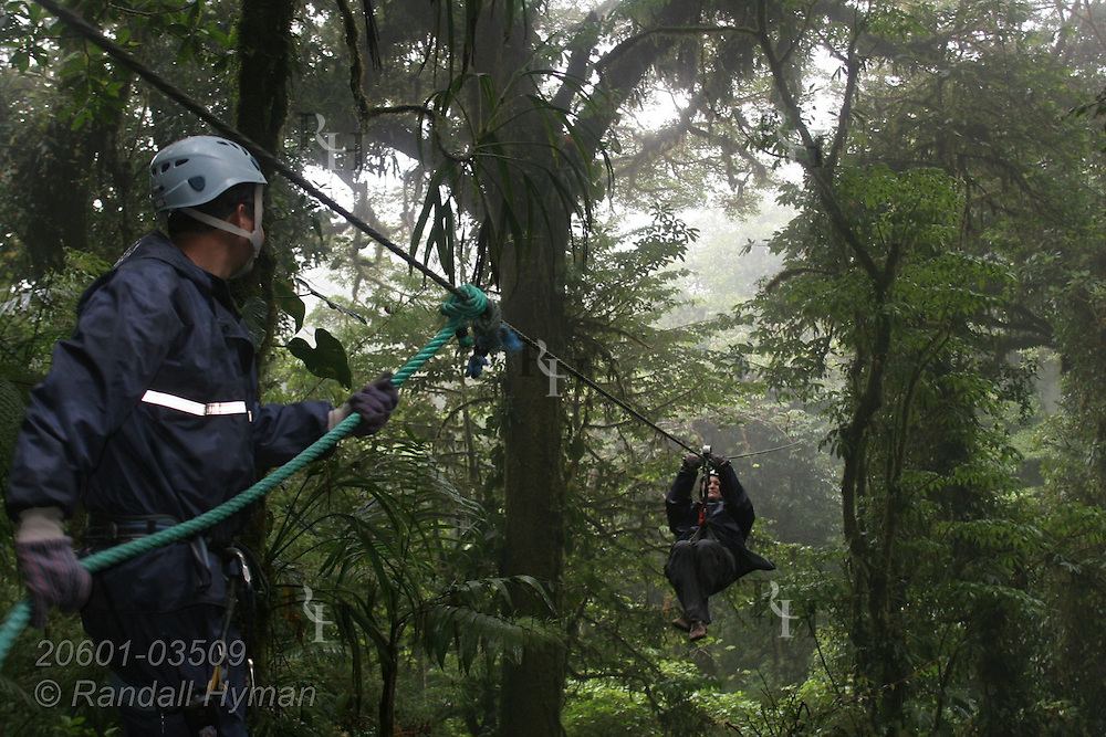 Ecoteach participant L'Ann Seibel ziplines through the Monteverde cloud forest on Sky Trek cable as guide awaits her arrival; Monteverde, Costa Rica.