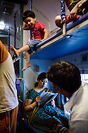 Train passengers in the a/c coach wait on board as the Himsagar Express 6318 halts for 40 mins at the Nizamuddin Station in Delhi on 7th July 2009.. .6318 / Himsagar Express, India's longest single train journey, spanning 3720 kms, going from the mountains (Hima) to the seas (Sagar), from Jammu and Kashmir state of the Indian Himalayas to Kanyakumari, which is the southern most tip of India...Photo by Suzanne Lee / for The National