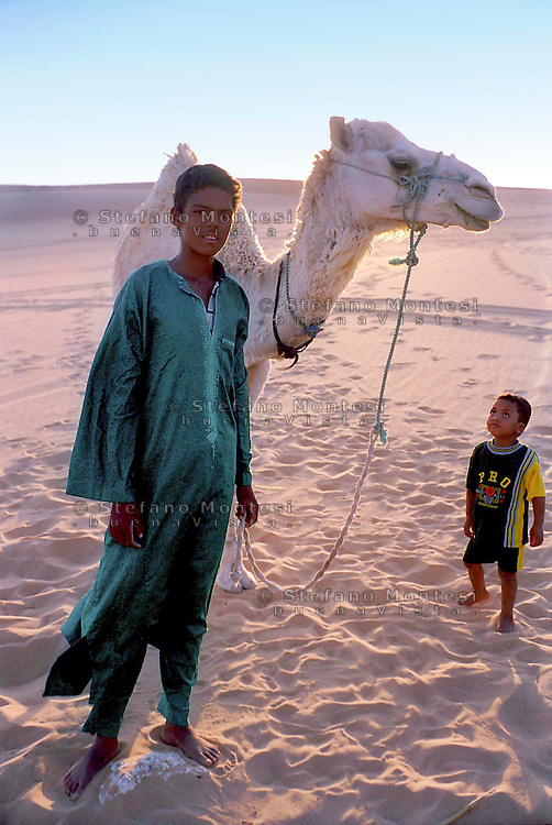 Libia, Ghadhames 2002.Ragazzo  Tuareg  con il  cammello nel deserto del Sahara.Libya, Ghadhames 2002.Tuareg boy with the camel in the Sahara