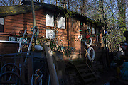 Converted from an old boat is a ramshackle artist's studio on Eel Pie Island on the River Thames, London. Eel Pie Island is an island in the River Thames at Twickenham in the Borough of Richmond upon Thames, London. It is situated on the Tideway and can be reached only by footbridge or boat. The island was known as a major jazz and blues venue in the 1960s. In 1969, the Eel Pie Island Hotel was occupied by a small group of local anarchists including illustrator Clifford Harper. By 1970 it had become the UK's largest hippie commune.