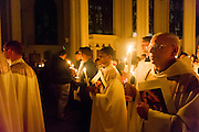 DENVER, CO - APRIL 19: The Rev. Roger Lascelle, right, processes with a lit candle during the Easter Vigil Mass at the Cathedral Basilica of the Immaculate Conception on April 19, 2014, in Denver, Colorado. (Photo by Daniel Petty/Denver Catholic Register)