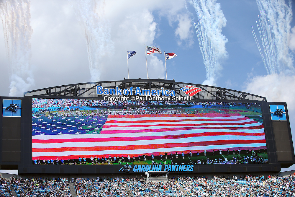 Fireworks fill the sky above the Bank of America Stadium scoreboard as a large American flag covers the field during the pregame show before the Carolina Panthers 2015 NFL week 2 regular season football game against the Houston Texans on Sunday, Sept. 20, 2015 in Charlotte, N.C. The Panthers won the game 24-17. (©Paul Anthony Spinelli)