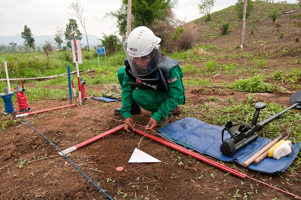 "Sokhon demonstrates testing her metal detector and the demining process in a safe zone at the MAG base camp at ""Koun Phnum"" or ""Baby Mountain"" minefield......Later inside the actual minefield, Sokhon's supervisor, Thor Thoeun, described the process while standing safely 25 meters away, watching.  With tension gripping his face, not wanting to disturb Sokhon, he whispers, ""We are always scared in the minefield.  When the detector signals Sokhon will pinpoint the spot with a red chip.""  Then she will excavate to find what is under it.  If Sokhon sees a mine she will place a red triangle pointing toward the danger.   Then she will blow a whistle for the supervisor to check the item.  If it is a land mine it will generally be destroyed in place.   ..Kheun Sokhon, age 29, is a female deminer for Mines Advisory Group (MAG), in Palin Province, Cambodia.  She searches for land mines - facing the same threat that shattered her life at age 19 - when she stepped on a mine.  She admits, ""I don't want people to experience what I have been through."" .."