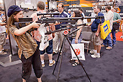 15 MAY 2009 -- PHOENIX, AZ: Alyssa Mahar (CQ) from Peoria, checks out a .50 caliber long range rifle at the convention Friday. More than 60,000 people are expected to attend the NRA convention and annual meeting, which is being held at the Phoenix Convention Center through Sunday. This is the 138th annual meeting of the National Rifle Association.  Photo by Jack Kurtz