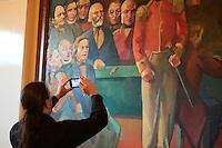 Member of the german Piraten Partei taking a photo of a painting inside Alþingi Parlament building in Reykjavík.