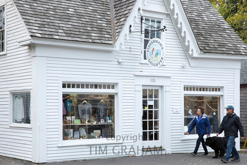 Couple and Newfoundland dog walk by Fisherman's Daughter clapboard store in High Street at Chatham, Cape Cod New England, USA