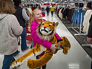 "28 NOVEMBER 2019 - ANKENY, IOWA: ELLIE VERSTEEG (VerSteeg), 8, from Ankeny, IA, carries a plush tiger toy she bought at the Target store in Ankeny, Iowa, Thursday evening. ""Black Friday"" is the unofficial start of the Christmas holiday shopping season and has traditionally thought to be one of the busiest shopping days of the year. Brick and mortar retailers, like Target, are facing increased pressure from online retailers this year. Many retailers have started opening on Thanksgiving Day. Target stores across the country opened at 5PM on Thanksgiving to attract shoppers with early ""Black Friday"" specials.     PHOTO BY JACK KURTZ"