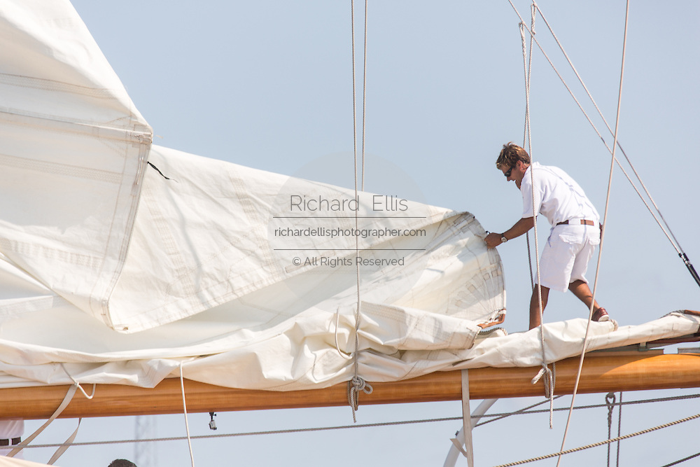 A deck hand rigs the sails on the 196-foot sailing yacht Germania Nova as it sails Charleston Harbor June 26, 2013 in Charleston, South Carolina.