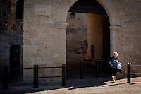 "SAN MARINO, SAN MARNO - 3 OCTOBER 2011:An elderly woman crosses the street by the ""Porta San Francesco"" (San Francesco Door) in San Marino, San Marino on October 3, 2011. The San Marino national football team is the last team in the FIFA  World Ranking (position 203). San Marino, whose population reaches 30,000 people, has never won a game since the team was founded in 1988. They have only ever won one game, beating Liechtenstein 1–0 in a friendly match on 28 April 2004. The Republic of San Marino, an enclave surronded by Italy situated on the eastern side of the Apennine Moutanins, is the oldest consitutional republic of the world<br /> <br /> <br /> ph. Gianni Cipriano"