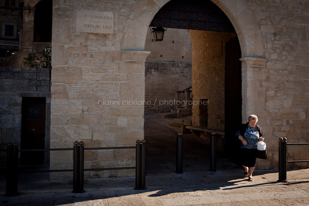 SAN MARINO, SAN MARNO - 3 OCTOBER 2011:An elderly woman crosses the street by the &quot;Porta San Francesco&quot; (San Francesco Door) in San Marino, San Marino on October 3, 2011. The San Marino national football team is the last team in the FIFA  World Ranking (position 203). San Marino, whose population reaches 30,000 people, has never won a game since the team was founded in 1988. They have only ever won one game, beating Liechtenstein 1&ndash;0 in a friendly match on 28 April 2004. The Republic of San Marino, an enclave surronded by Italy situated on the eastern side of the Apennine Moutanins, is the oldest consitutional republic of the world<br /> <br /> <br /> ph. Gianni Cipriano