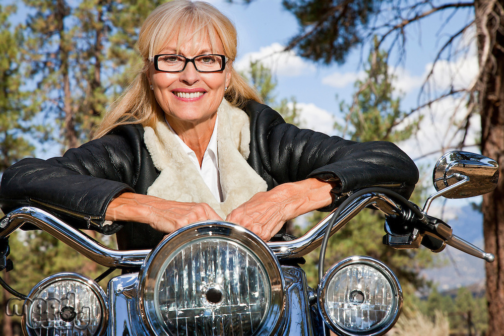 Senior woman leaning on motorbike handlebars