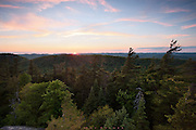 Rondaxe Mountain, Adirondacks, NY.<br /> Every summer for a few days, my parents packed car, kids and supplies for the trek to Raquette lake in the Adirondacks.  There, my dad's brothers and sisters had camps, and all of us cousins ran wild over lake and land.  Every year we passed by the Bald Mountain Fire Tower sign, and every year I begged to stop the car and go up there.  One year--I was probably 8 or 9-- my dad slowed and turned up the road to the trailhead, looked at my brother and I and said let's go.  And so we did while my mother and baby brother stayed behind.  It isn't a long hike, but seemed a big adventure back then.   I had a terrible fear of heights as a child, and I remember getting just so high and freezing, having to go a step at a time on my fanny, both up and down, clinging to steps and rails for safety.  Up on the platform, I was fine,  thrilled by the Ranger in the cab of the structure, dutifully scanning  (I imagined) that big horizon for fires, ready to be on it before the whole place could go up in smoke. It wasn't until 30 years later, when I began hiking and photographing seriously, that I overcame my fear of heights, at least for the most part. The Rangers don't man the cabs anymore, and on this night I had the place to myself for the sun's final wink before dipping beyond.  It was a while after dark and the last color before I made my way down, upright, thinking about the visit so many years ago, and how, to be honest, there are still a few taller towers that I cling to rails and steps for dear life, till the feeling passes.