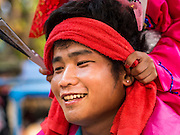 "05 APRIL 2015 - CHIANG MAI, CHIANG MAI, THAILAND: A Tai Yai man carries a Buddhist novice on his shoulders during the second day of the three day long Poi Song Long Festival in Chiang Mai. The Poi Sang Long Festival (also called Poy Sang Long) is an ordination ceremony for Tai (also and commonly called Shan, though they prefer Tai) boys in the Shan State of Myanmar (Burma) and in Shan communities in western Thailand. Most Tai boys go into the monastery as novice monks at some point between the ages of seven and fourteen. This year seven boys were ordained at the Poi Sang Long ceremony at Wat Pa Pao in Chiang Mai. Poy Song Long is Tai (Shan) for ""Festival of the Jewel (or Crystal) Sons.    PHOTO BY JACK KURTZ"