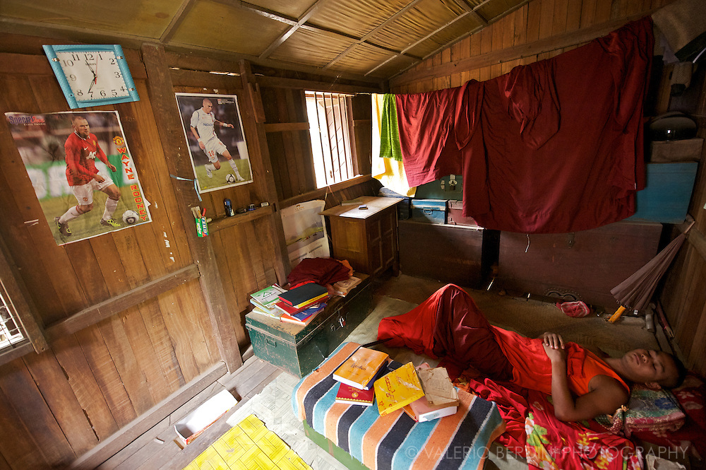A young monk sleeps in his room surrounded by books, clothes, the umbrella and posters of his football heroes. Samaneras live according to the Ten Precepts, but are not responsible for living by the full set of monastic rules (vinaya).