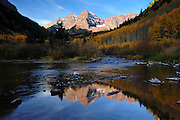 Early light on the peaks gently reflected in Maroon Creek while the turning aspens are still in shadow.