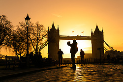 © Licensed to London News Pictures. 22/12/2018. London, UK.  Tourists take photographs in front of  Tower Bridge shortly after sunrise, as the capital is experiencing milder and sunny weather this morning.  Photo credit: Vickie Flores/LNP