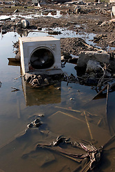 30 Sept, 2005.  New Orleans, Louisiana. Lower 9th ward. Hurricane Katrina aftermath. <br /> The remnants of the lives of ordinary folks, now covered in mud as the flood waters remain. The contents of a washing machine lie scattered in the toxic flood waters.<br /> Photo; ©Charlie Varley/varleypix.com