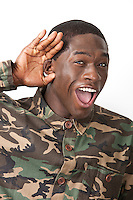Portrait of cheerful young military soldier in camouflage clothing with hand behind his ear against white background