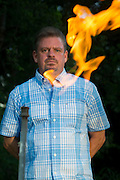 Steve Lipsky shows the methane contamination of his well by igniting the gas with a lighter outside his family's home in Parker County near Weatherford, Texas on June 17, 2014. (Cooper Neill / for The Texas Tribune)