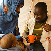 Médecins Sans Frontières (MSF) health promotion manager, Barry Mamadou Kaba, helping M'barka Mint Albataly feed a nutritional supplement to her malnourished daughter, Salka Mint Youba (6 months), at an MSF health post at the Mbera camp for Malian refugees in Mauritania, on 10 March 2013.