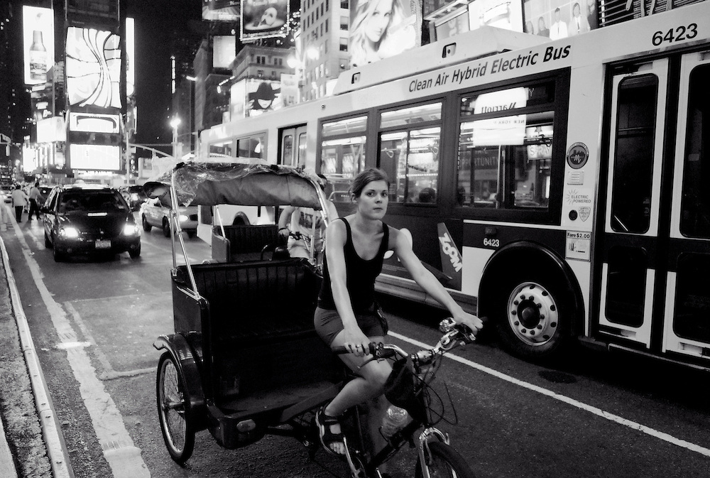 Woman driving pedicab next to MTA hybrid electric bus during hot, summer night in Times Square, New York City, 2007