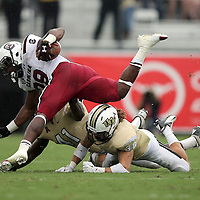 South Carolina Gamecocks running back Mike Davis (28) gets tackled by UCF Knights linebacker Terrance Plummer (41) and UCF Knights defensive back Jordan Ozerities (38) during an NCAA football game between the South Carolina Gamecocks and the Central Florida Knights at Bright House Networks Stadium on Saturday, September 28, 2013 in Orlando, Florida. (AP Photo/Alex Menendez)