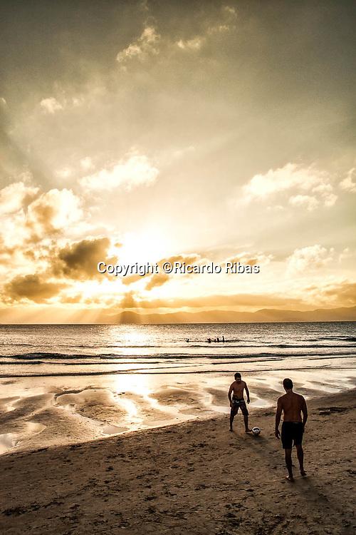 Silhueta de homens jogando futebol na Praia de Ponta das Canas. Florianópolis, Santa Catarina, Brazil. / Silhuette of men playing soccer at Ponta das Canas Beach. Florianopolis, Santa Catarina, Brazil.